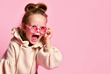 Naughty girl with tall hair dressed in pink hoodie yelling angrily resettling spectacles on face. Close up shot isolated on pink, copy space. Fashion for children, facial expression, capricious kid