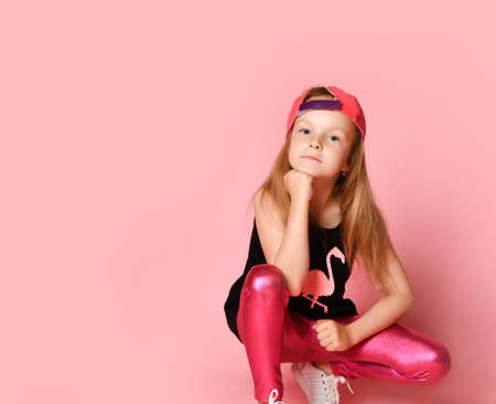Charming active preschool girl in a fashionable fashionable dress, playful and smiling, squatting, looking at you with her fist propped on her head. on a pink background