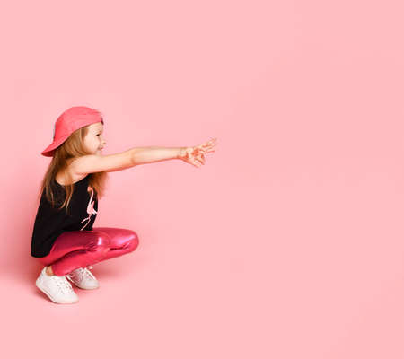 Carefree cheerful smiling happy blonde little girl turns left, pointing fingers at pistols with both hands, copy space
