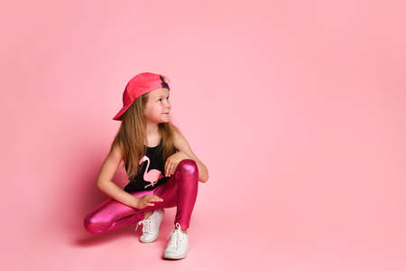 Charming active preschool girl in a trendy fashionable outfit, playful and smiling, squatting and looking to the side on a pink background. Stylish kids, happy childhood, emotions, games and fun Фото со стока