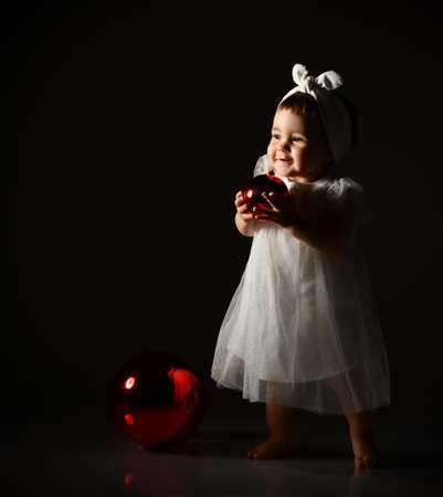 Little kid in white headband and dress, barefoot. She posing with two red balls, christmas decoration, standing in twilight, on black background. New Year, holidays. Close up, copy space, side view Фото со стока