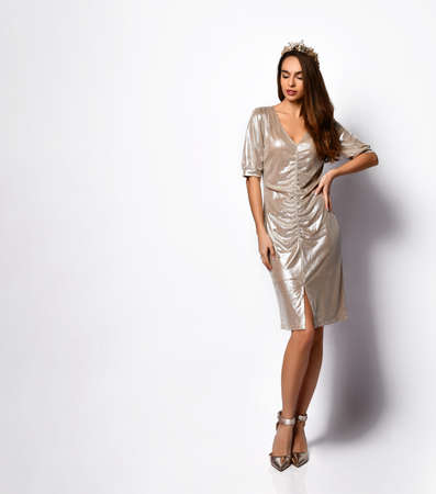 delightful young woman in a short silver dress and shoes with a diadem on her hair. Women's fashion, charm, beauty, stylish look, femininity. Posing on a light background Stockfoto