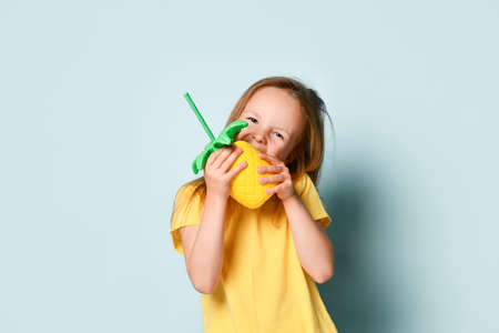 Cute little girl in sunny yellow t-shirt making a show of biting bright inflatable pineapple. Waist up shot isolated on light blue, copy space. Children, happiness, cute and positive , summer time