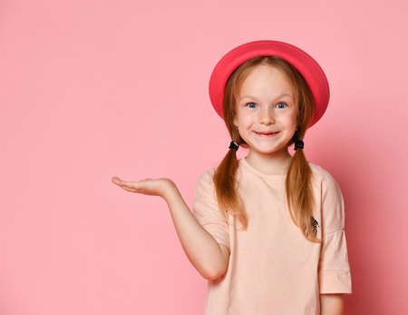 Funny blonde child in hat and t-shirt. She is smiling and acting like holding something on her palm. Posing against pink studio background. Childhood, emotions, advertising. Close up, copy space