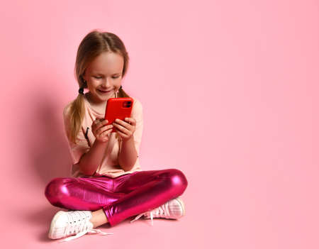 Blonde little girl in t-shirt, leggings and sneakers. She smiling, using her red smartphone while sitting on floor with crossed legs against pink background. Modern technologies. Close up, copy space
