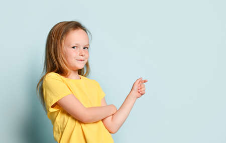 Cute blonde little girl in a yellow T-shirt. She smiles and points to the side with her index finger, looks at you. Presenting on a turquoise studio background.