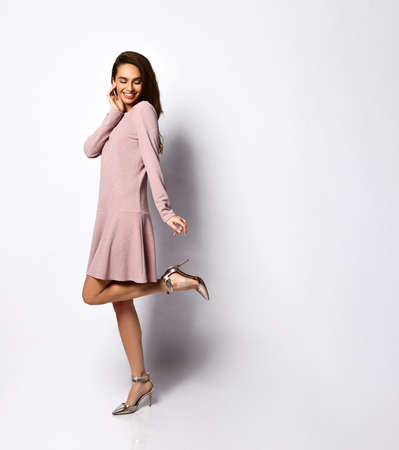 slender, beautiful woman raised her leg in elegant silver high-heeled shoes and a pink mini dress on white. Beauty and style, elegance, fashionable shoes for ladies. Copy space Reklamní fotografie