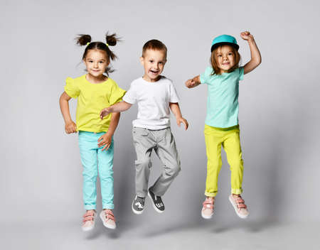 Three excited kids in fashion outfits, jumping over the light background. Two sisters and brother, friends in fashionable clothes. Фото со стока