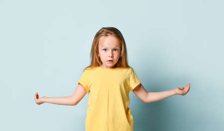 Adorable blonde kid in yellow t-shirt. She spreads her hands wide apart like holding something and looking surprised while posing against turquoise studio background. Close up, copy space