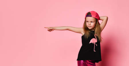 cute girl in a pink cap, on the contrary, and leggings points a finger at something interesting to the side. on a pink studio background