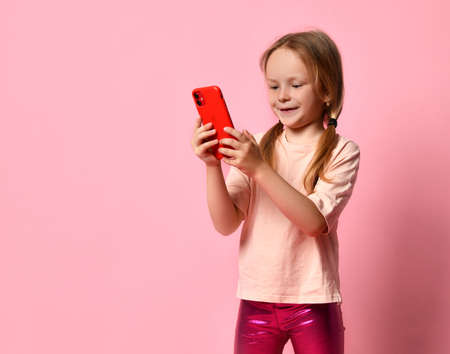 Pretty little girl in two ponytails has fun chatting on her red smartphone against a pink wall Фото со стока