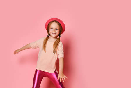 Full length portrait of a crazy cheerful girl in summer clothes and hat listening to music, and dancing isolated on a pink background