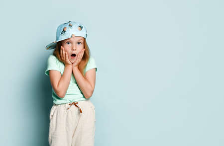 Surprised blond child in a T-shirt, white pants and a cap with a picture of pineapples. She opened her mouth and looked shocked, posing against the turquoise studio background. Close copy space