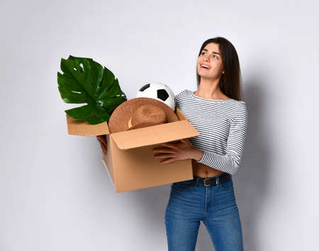 Young attractive brunette girl holding a cardboard box with things - plant, hat, ball and others. A woman is infinitely happy to move to her new dream home.