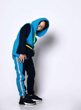 Cute smiling boy in a modern cotton tracksuit with a cute haircut, putting a hood on his head fooling around on a light background.