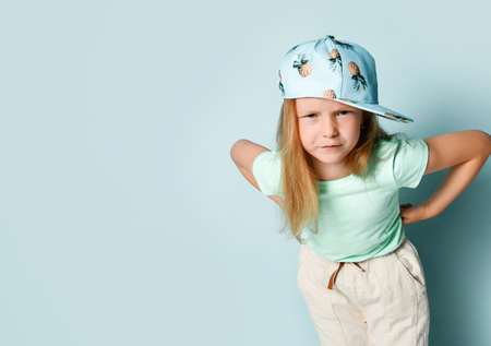 Angry little girl standing with hands on hips, bending her eyebrows and looking angrily. Cropped studio shot isolated on light blue, copy space. Stylish children, emotions, expression, summer time