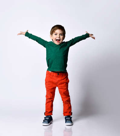 Fashion handsome boy in a green t-shirt raising his hands and looked very pleased, posing isolated on a white background. Childhood, fashion, advertising.