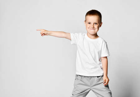 ittle cute preschooler boy shows his hand to the side, in a white T-shirt and gray pants. Place for your advertising