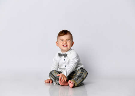 Happy baby. Little boy in a white shirt and bow tie. Children portrait. Stylish man in fashionable a bow-tie.