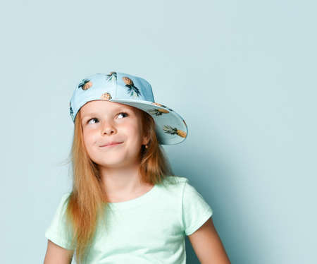 Portrait of a cheerful young stylish girl in a cap looks up on a blue background