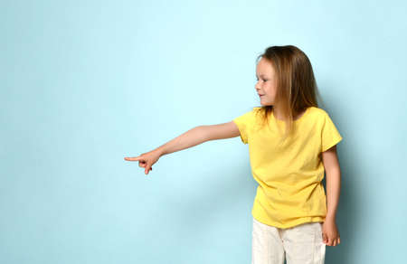 Adorable blonde little girl in a yellow shirt shows her hand on the free space of the frame.. Close up, copy space Фото со стока