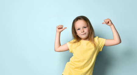 Confident little preschool girl posing in yellow t-shirt pointing with thumbs at herself. Waist up shot isolated on light blue, copy space. Children, gestures and emotions, summer time, I am the best