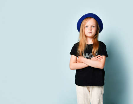 Cute blonde child in blue hat, black t-shirt and white pants. She is looking at you with crossed hands while posing against turquoise studio background. Childhood, fashion, advertising. Copy space