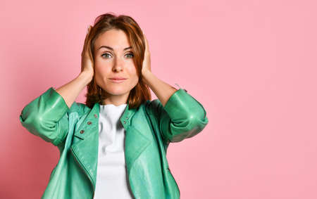 Beautiful upset woman posing, isolated on light pink background of wall covering ears. Фото со стока