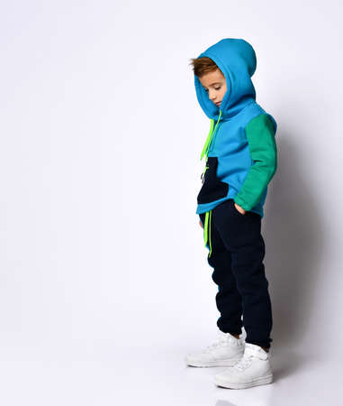 Side view shot of little schoolboy in bright cotton tracksuit standing with hands in pockets looking down. Children fashion, young athletes, being stylish. Full length portrait isolated on light grey Фото со стока