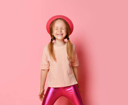 Cute little girl in trendy summer attire and hat standing and laughing while keeping eyes closed. Three quarter length shot isolated on pink, copy space. Children, gestures and emotions, hide and seek Фото со стока