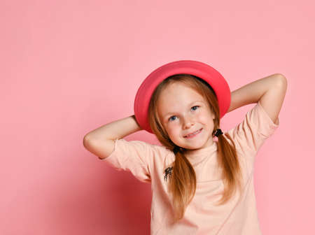 Funny blonde kid in hat and t-shirt. She is smiling, putting hands behind her head and looking up dreamily. Posing against pink studio background. Happy childhood, emotions. Close up, copy space