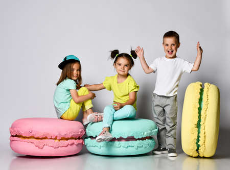 Three friends of triplets - two girls and a boy in bright clothes have fun at the birthday party fun room decoration candy macarons.