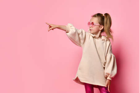 Concentrated little girl in casual pink attire looking aside pointing her finger at someone. Studio shot isolated on pink, copy space. Stylish kids, childhood, emotions, challenging, do it