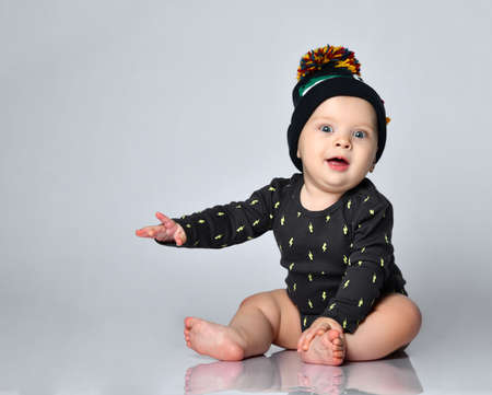Baby boy in black bodysuit and hat with crocodile print, barefoot. He is sitting on floor isolated on white studio background. Concept for articles about childhood or advertising for babies. Close up Фото со стока