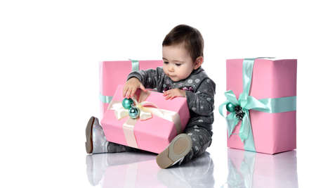 Baby girl in gray suit with snowflakes print, boots. She playing with decoration on pink gift box, sitting on floor isolated on white background. Christmas, New Year, birthday. Close up, copy space
