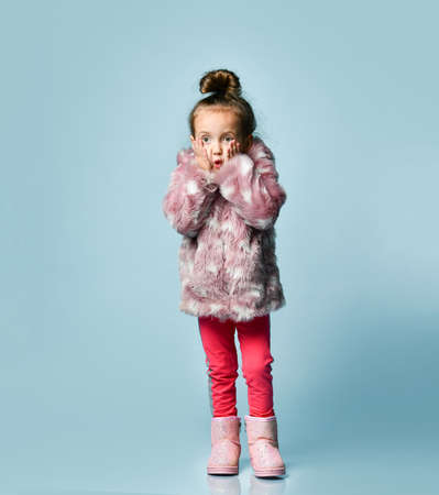 Little blonde kid with bun hairstyle, dressed in pink faux fur coat. She is looking excitedly while posing against blue studio background. Childhood, fashion, advertising. Close up, copy space