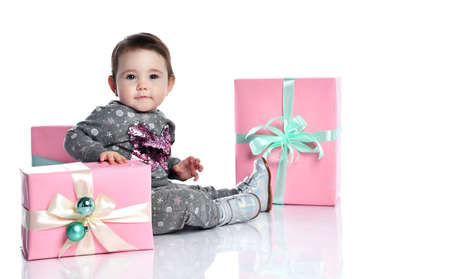 Toddler in gray suit with snowflakes print and boots. She smiling, posing with decorated gift boxes, sitting on floor isolated on white background. birthday. Close up, copy space Фото со стока