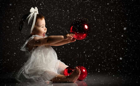 Girl in a white headband and barefoot dress. She holds two red balls in front of her, sits on the floor. Twilight, black studio background. New year, holidays. Snowing