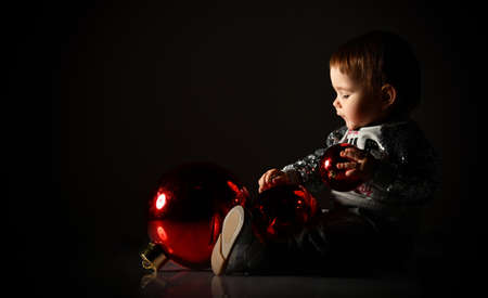 Toddler in gray boots and sparkling suit. She is playing with three red balls, christmas decoration, sitting on floor in twilight, against black background. New Year, holidays. Close up, copy space