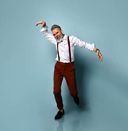 Gray-haired elderly man in white shirt, brown pants and suspenders, black loafers. He is smiling, running, waving his hands, posing on blue background. Fashion and style. Full length, copy space Фото со стока