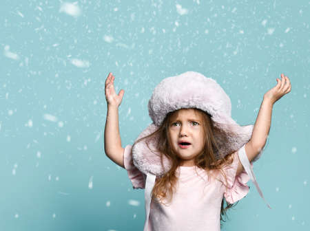 Little blond kid with long hair, dressed in a pink blouse, a plush hat with earflaps. She raised her hands, looking confused, posing on a blue background in snowfall.