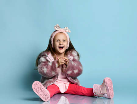 Little child with headband, dressed in pink faux fur coat, pants and boots. She smiling, legs and arms apart, sitting on floor against blue background. Fashion, advertising. Close up, copy space Фото со стока