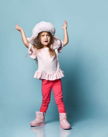 Little blonde kid with long hair, dressed in pink blouse, plush hat, pants and boots. She raised her hands, looking confused, posing on blue background. Fashion, advertising. Full length, copy space Фото со стока