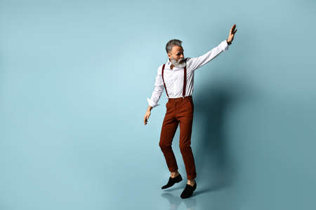 Gray-haired man in years in white shirt, brown pants and suspenders, black loafers. He runs looking back, showing stop sign by his hand, posing on blue background. Full length, copy space