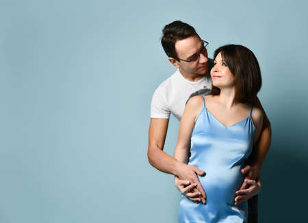 Brunette pregnant female in blue silk dress or nightie. Her husband is hugging her, they looking at each other and smiling, put hands on her belly, posing on blue background. Close up, copy space