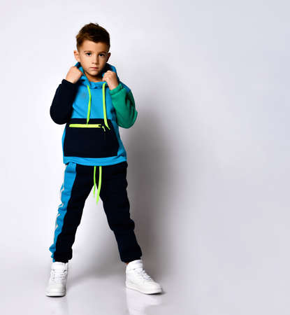 Serious boy in stylish cotton jym suit standing with legs apart keeping hands in pockets. Children athletes, active lifestyle, fashion sportswear design. Full length portrait isolated on light grey Фото со стока