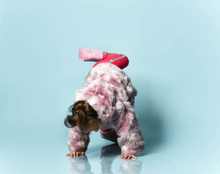 Little girl with a bun hairstyle, dressed in a pink fur coat, trousers and boots. She is fooling around, indulging, trying to stand up on a blue studio background. Childhood, fashion, advertising. Full length, copy space Фото со стока