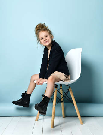 curly little girl with hairstyle, in beige dress, black jacket and boots. She is screaming, sitting on white chair against blue studio background. Childhood, fashion. Full length, copy space