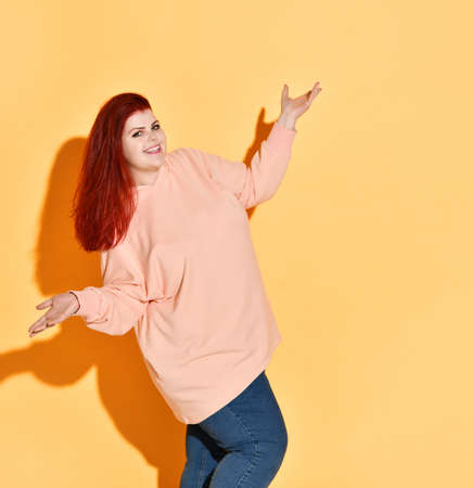 Excited smiling young chubby lady is happy of her achievement, showing voila gesture with open palms. Success, motivation, trendy, chubby lady, diet, self-acceptance. Studio shot isolated on orange.