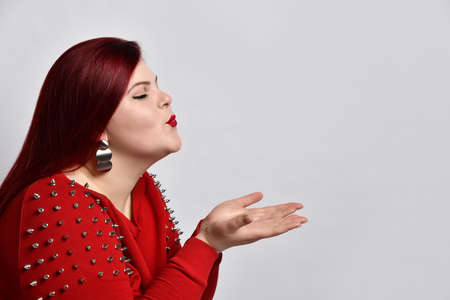 Fat ginger female in red spiked blouse and earrings. She has closed her eyes and sending an air kiss while posing sideways isolated on white background. Fashion and style concept. Close up, copy space